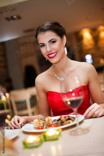Beautiful woman eating in restaurant