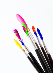 Six paint brushes with gouache isolated on white