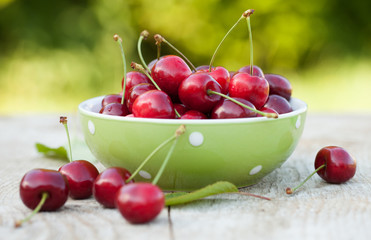 Fresh cherries in a bowl on garden table