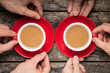 Hands Taking Two Red Cups of Coffee on old Wood Background