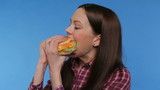 beautiful girl eating a big hamburger