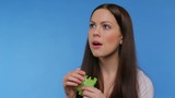 girl eats lettuce thinks and makes a funny face