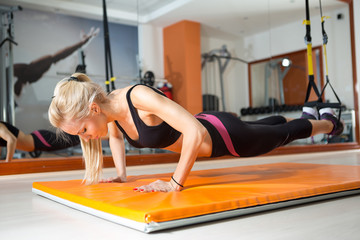 Young woman looking down while doing push-ups