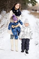 Happy family enjoying a walk in winter park