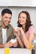 Happy couple with coffee cup in kitchen