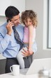 Well dressed father using cellphone while carrying his daughter