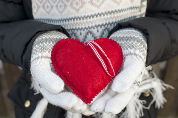 Girl hands in white knitted mittens with romantic red heart