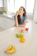 Woman eating apple with fruits on kitchen counter