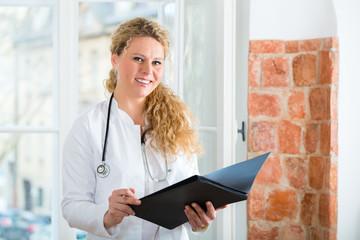 Ärztin in Praxis liest Krankenakte
