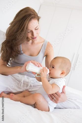 Fototapeta Mother feeding baby with milk bottle