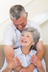 Senior man hugging wife sitting on sofa