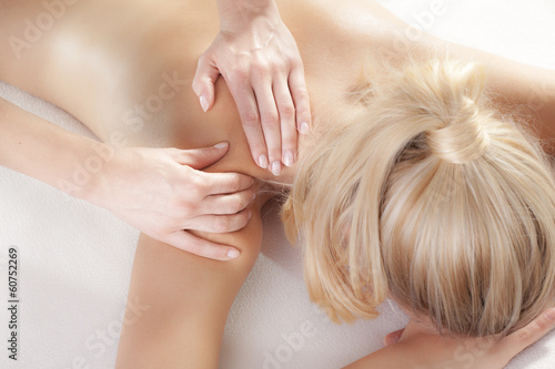 woman giving back massage to a girl - 60752269
