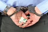 Man in handcuffs holds money in his palms behind his back