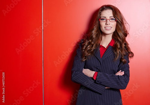 Portrait of a cute young business woman smiling. Red wall backgr
