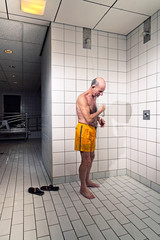 Senior man taking a shower in bathroom. Wearing yellow swimming