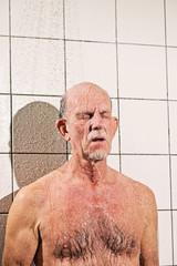 Senior man taking a shower in bathroom.