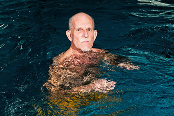 Healthy senior man with beard in indoor swimming pool.