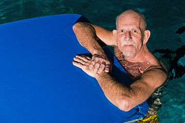 Healthy active senior man with beard in indoor swimming pool pla