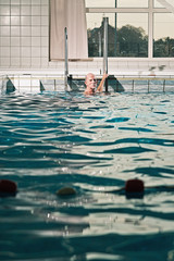 Healthy active senior man with beard in indoor swimming pool.