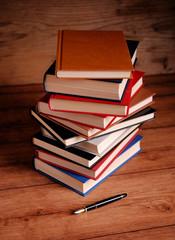 pila di libri con la penna stilografica sul tavolo di legno