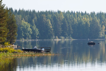 landscape with motor boat on the coast of lake, Finland