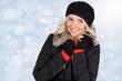 Lachende junge blonde Frau im Schnee