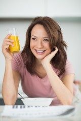 Woman with a bowl of cereals, orange juice and newspaper in kitc