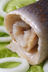 herring roll with onion rings on lettuce closeup. vertical