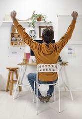 Modern creative man celebrating a success on workspace.