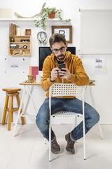 Modern creative man with smartphone on workspace.