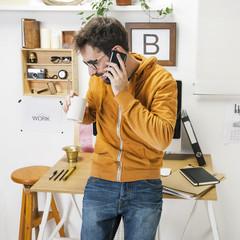 Modern creative man talking with smartphone on workspace.