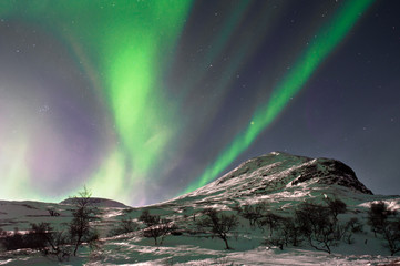 Northern lights above mountain hill. Captured near Skibon, Norwa