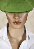 Head of a female mannequin wearing a green hat.