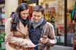 Touristen in Stadt mit Stadtplan und Smartphone