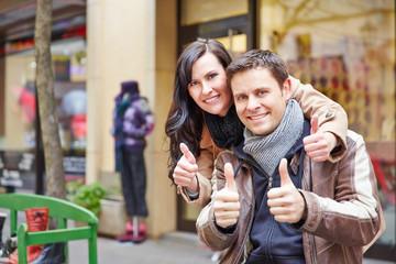 Paar in Stadt hält Daumen hoch