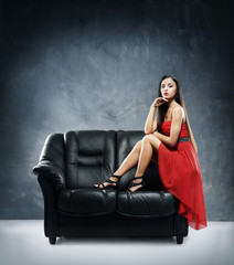 A glamour woman in red dress sitting on a black leather sofa