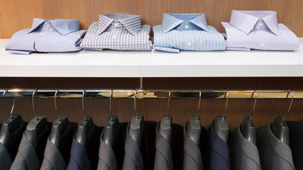 Row of men suit jackets on hangers and shelf with shirt in cloth