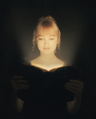Woman reading a glowing Bible.