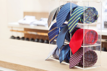 set of rolled up neck ties on plastic shelf