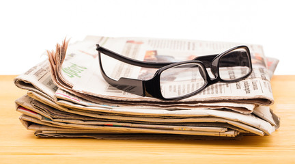 pile of newspapers and reading glasses