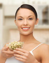 healthy woman holding bowl with sprout