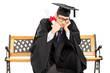Worried student in graduation gown on bench holding diploma