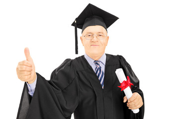 Mature man in graduation gown holding a diploma, giving thumb up