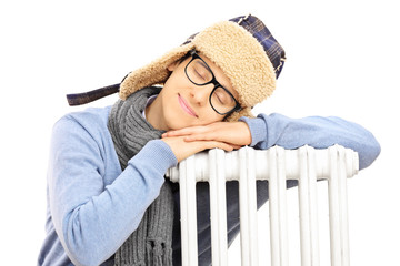 Young man in winter hat sleeping on a radiator