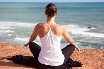 Yoga exercise sitting cross-legged rear view