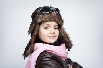 Portrait of a pilot child against gray background