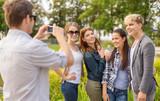 teenagers taking photo digital camera outside