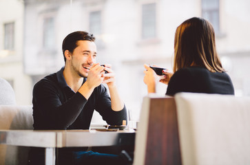 Couple drinking coffee laughing in cafe