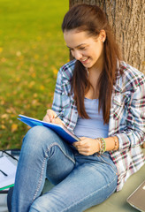 smiling teenager writing in notebook