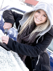 Smiling woman scraping ice from car window